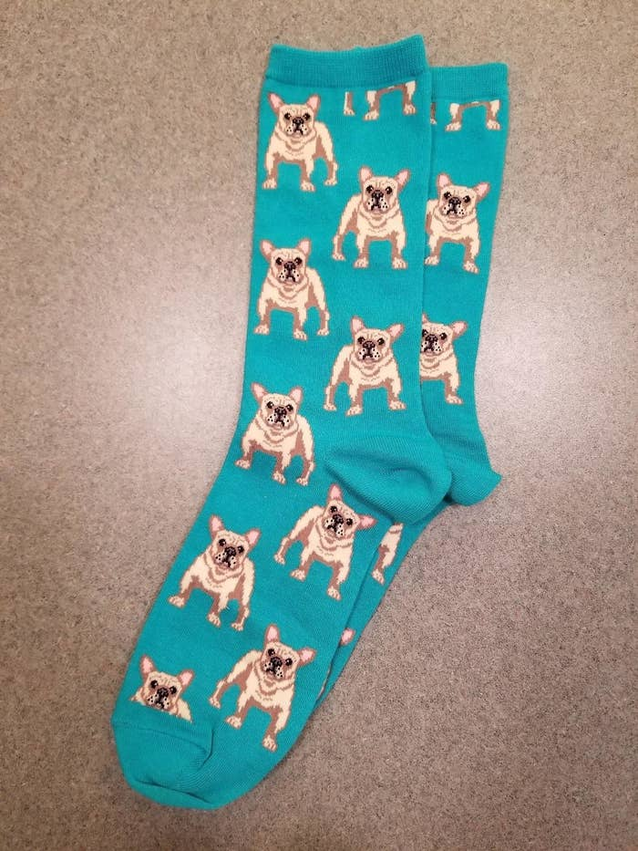 Reviewer pic of the teal socks with illustrations of yellow Frenchies all over them