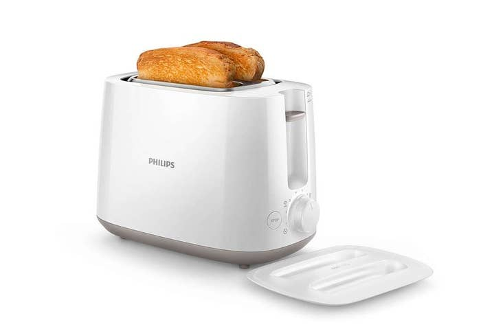 A white toaster with 2 pieces of toast in it