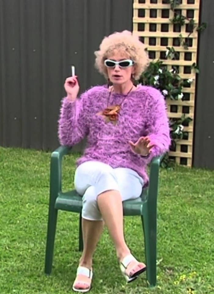 Woman sitting on a plastic lawn year wearing a pink jumper and sunnies, smoking a cigarette