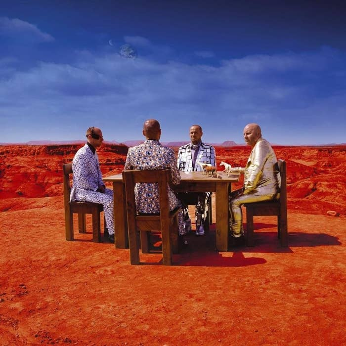 Four men dressed in patterned suits sitting at a dining table in the desert