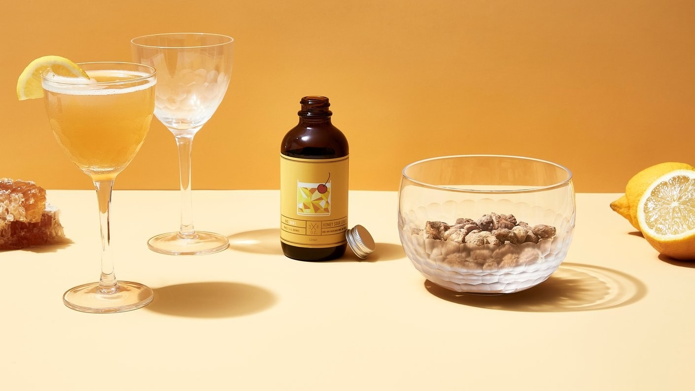 Two wine-shaped glasses, one with liquid in it, a bottle, and a glass cup with peanuts in it