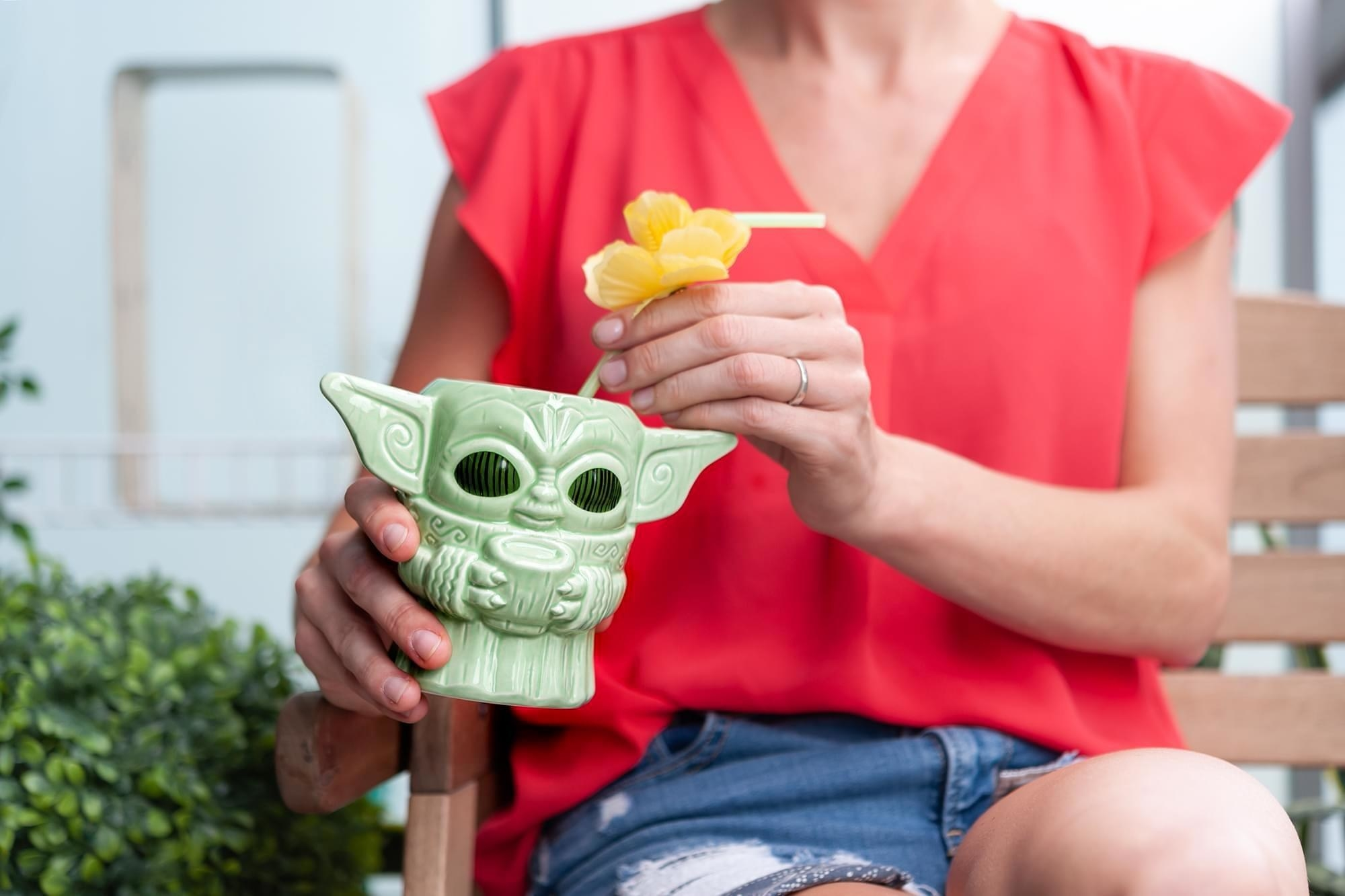 Model holding the tiki mug that looks like Baby Yoda in all green