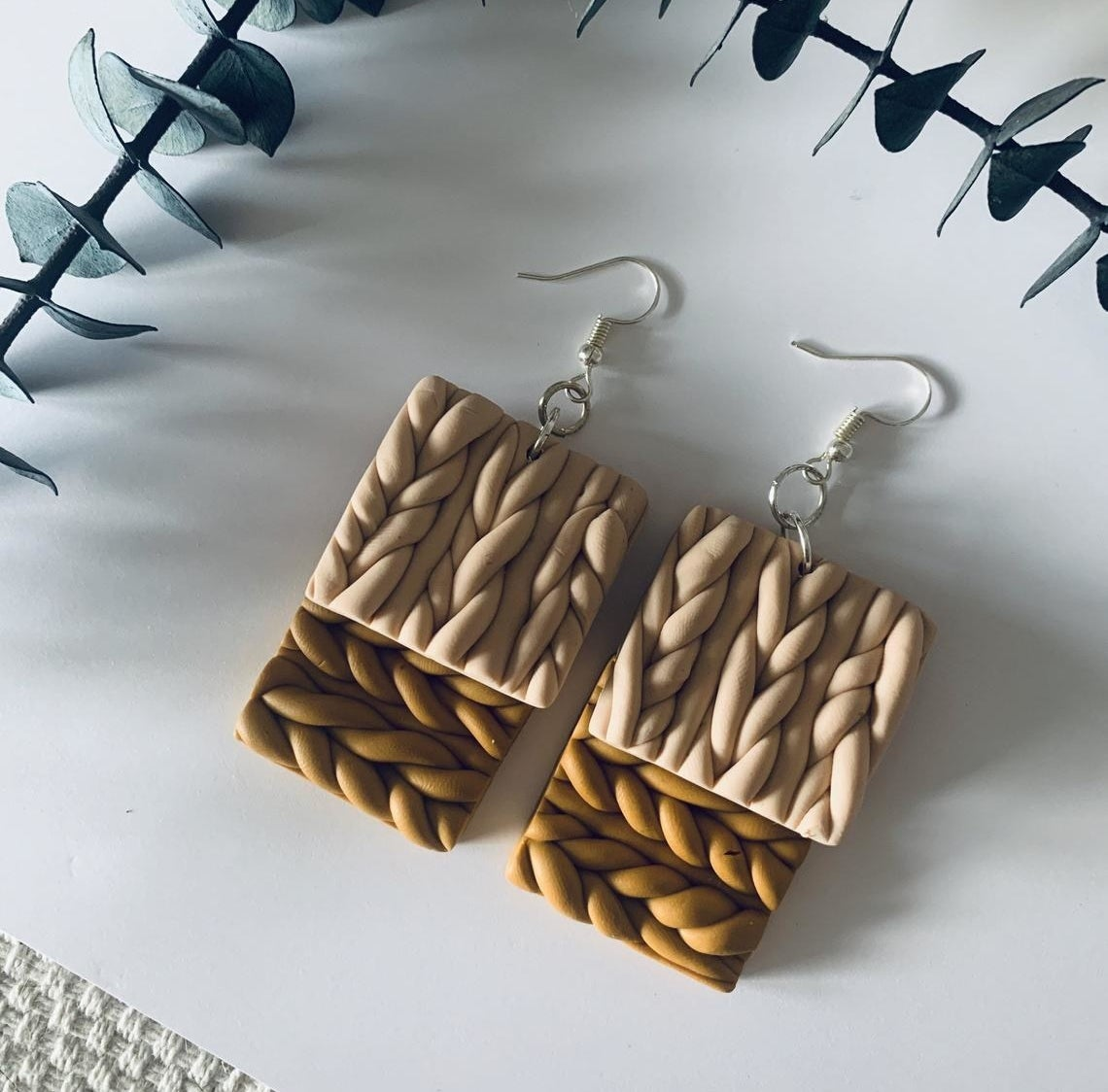 Two pairs of dangly cable knit earrings on top of each other
