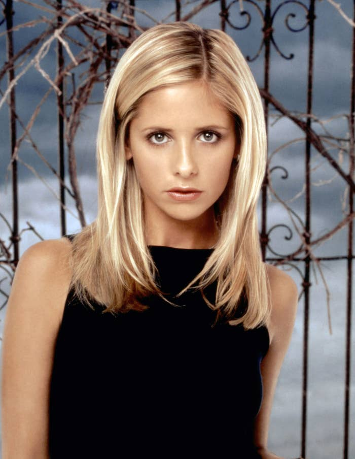 Sarah Michelle Gellar poses as Buffy the Vampire Slayer in front of a fence