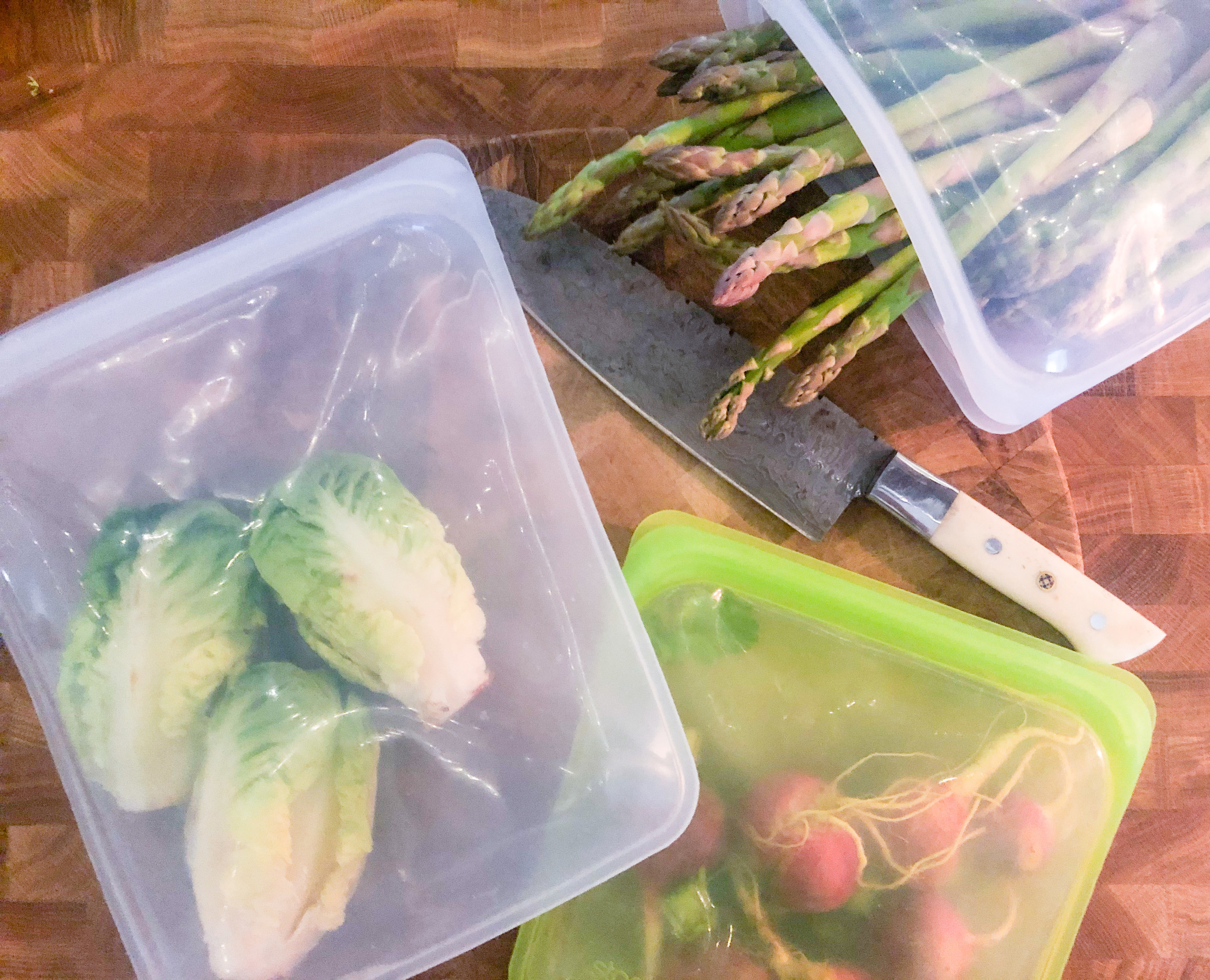 A flatlay of the silicone bags, all containing fresh produce, like radishes, lettuce, and asparagus