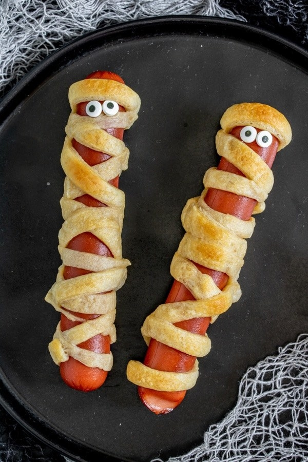 Two mummy dogs, hot dogs wrapped in crescent roll dough with candy eyes, on a plate.