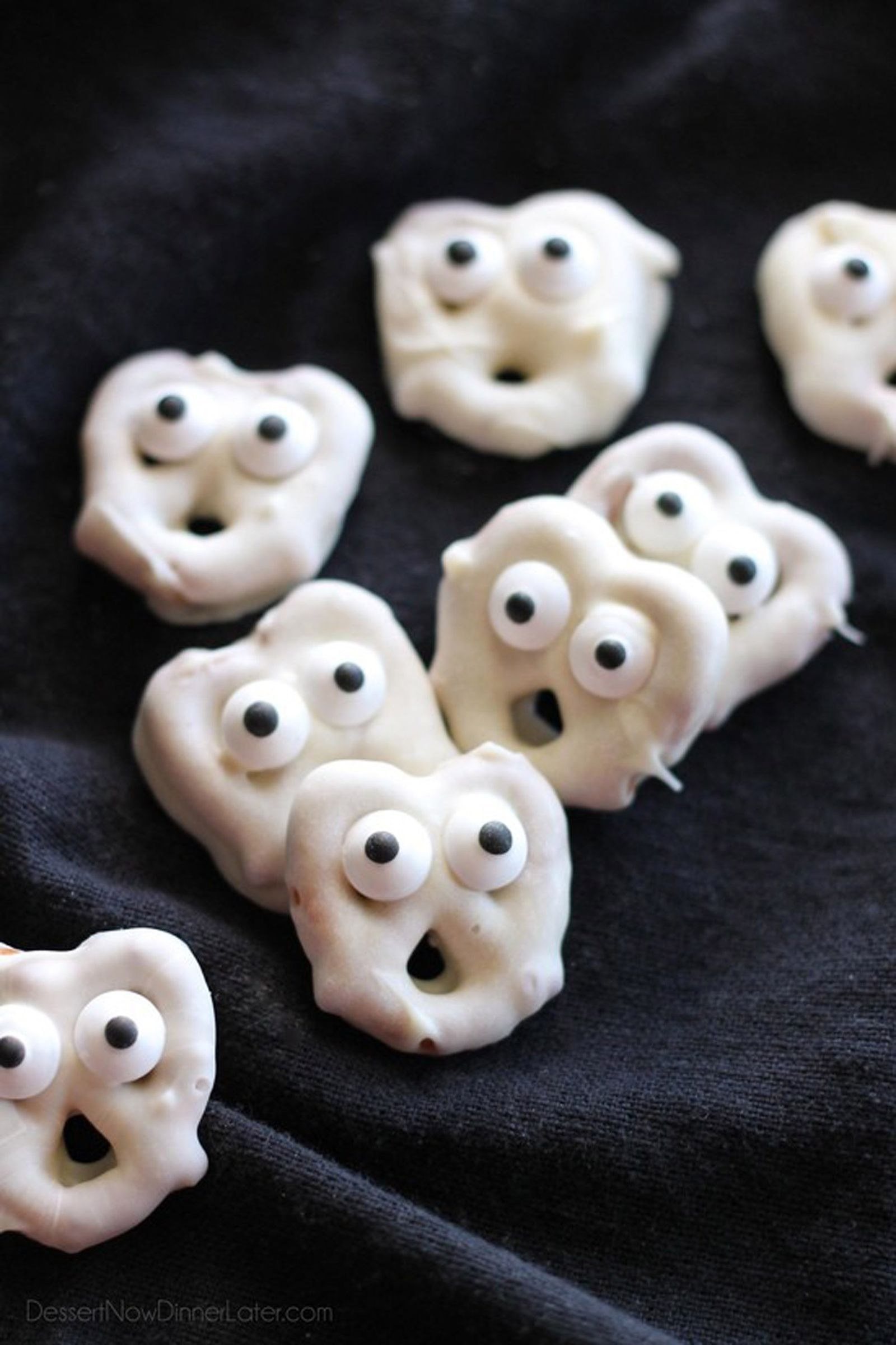 A handful of white-chocolate dipped pretzels with candy eyes.