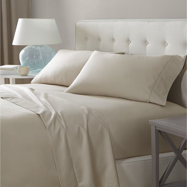 cream sheets and pillow cases on a bed