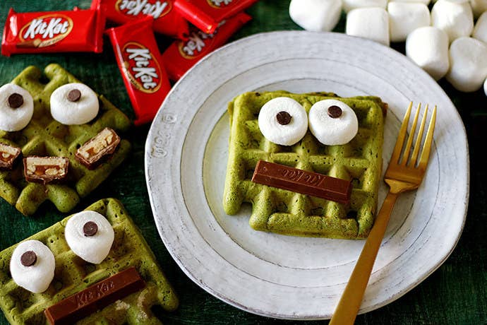 Homemade matcha monster waffles decorated with KitKat bars, marshmallows, and chocolate chips.
