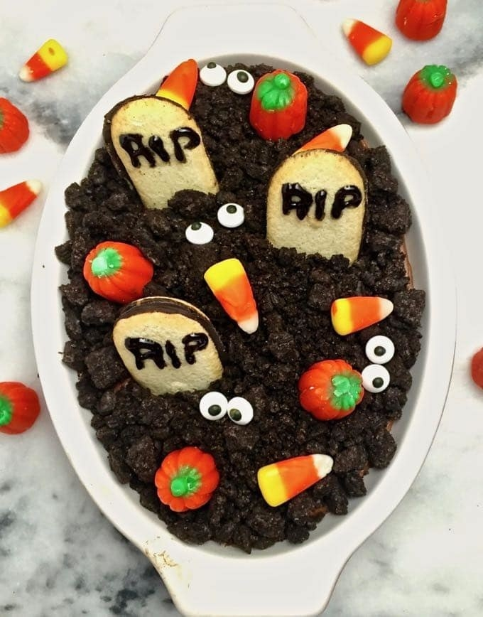 A serving dish filled with chocolate cheesecake graveyard dip.