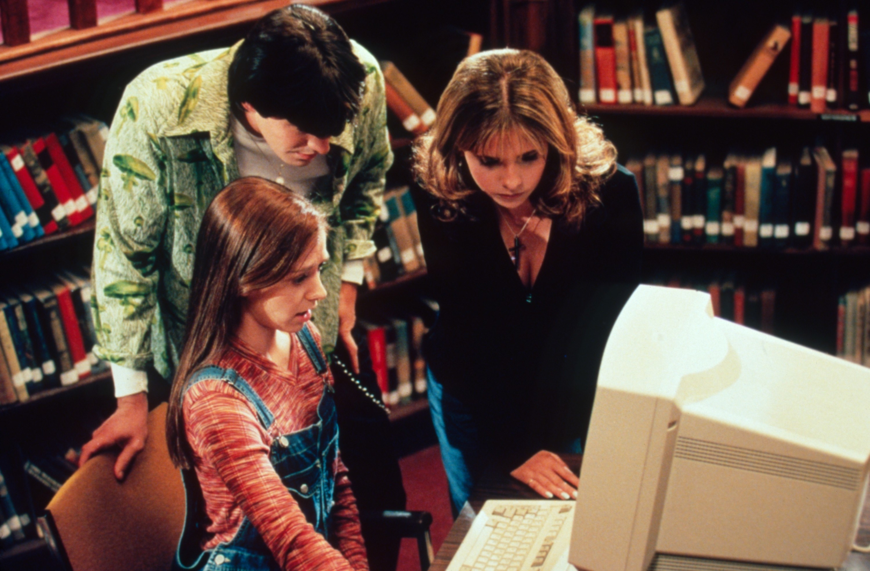 Buffy, Willow, and Xander look at a computer in front of a bookcase
