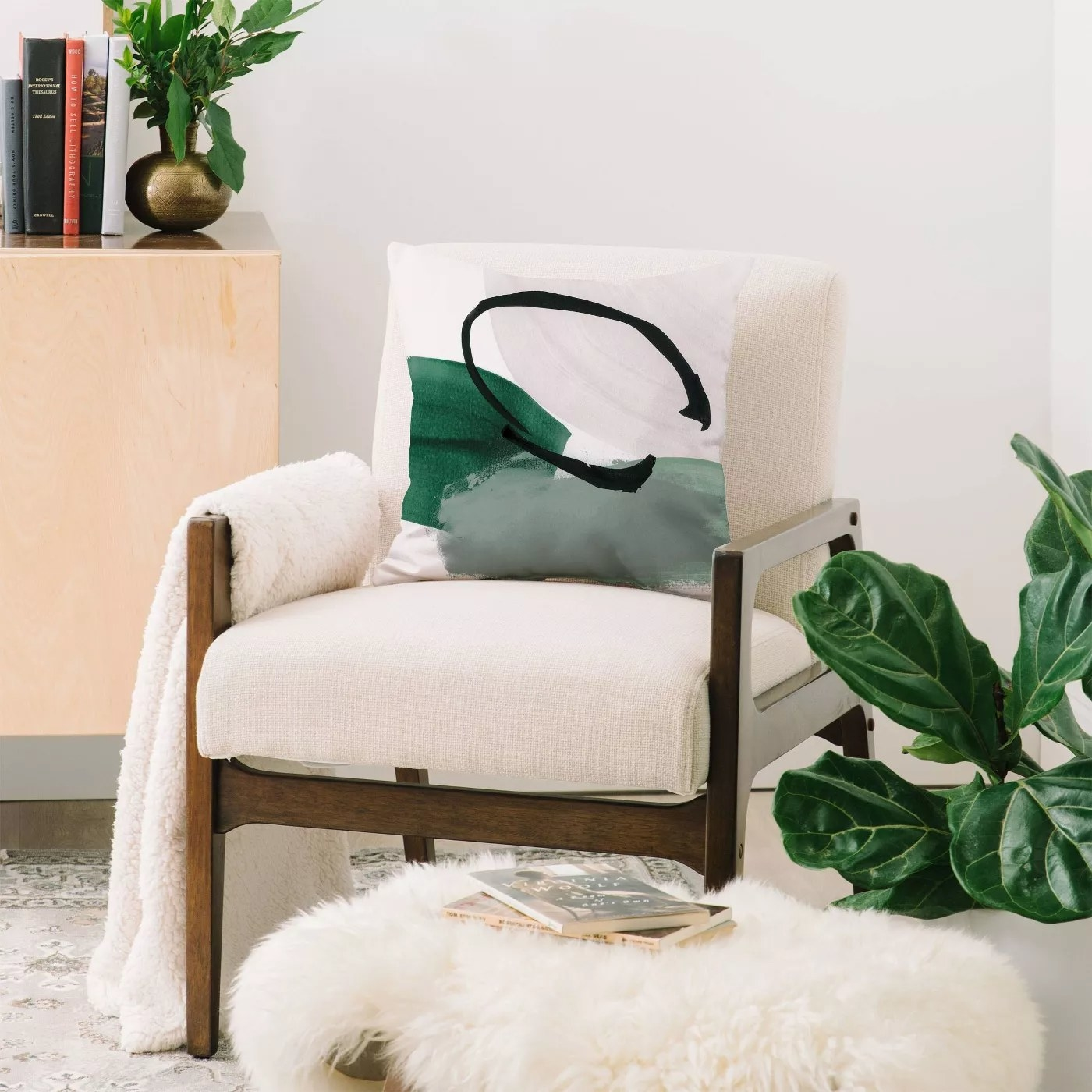 The throw pillow with a green and white paint design cover