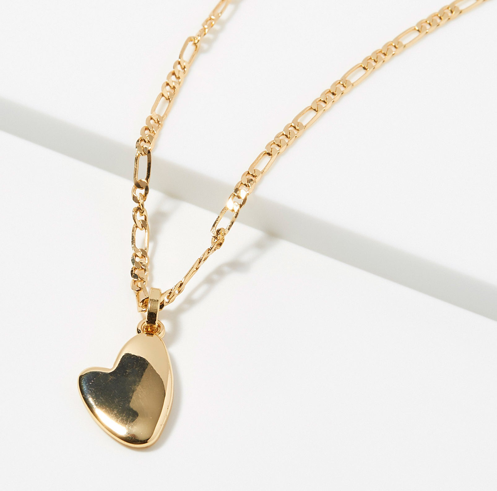A gold chain necklace with a heart-shaped pendant