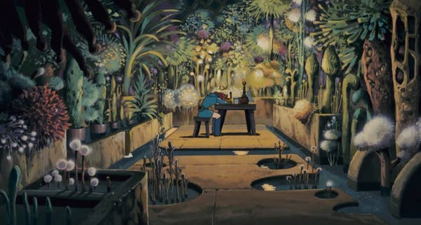 A girl at a desk in the middle of a room with an abundance of unusual plants