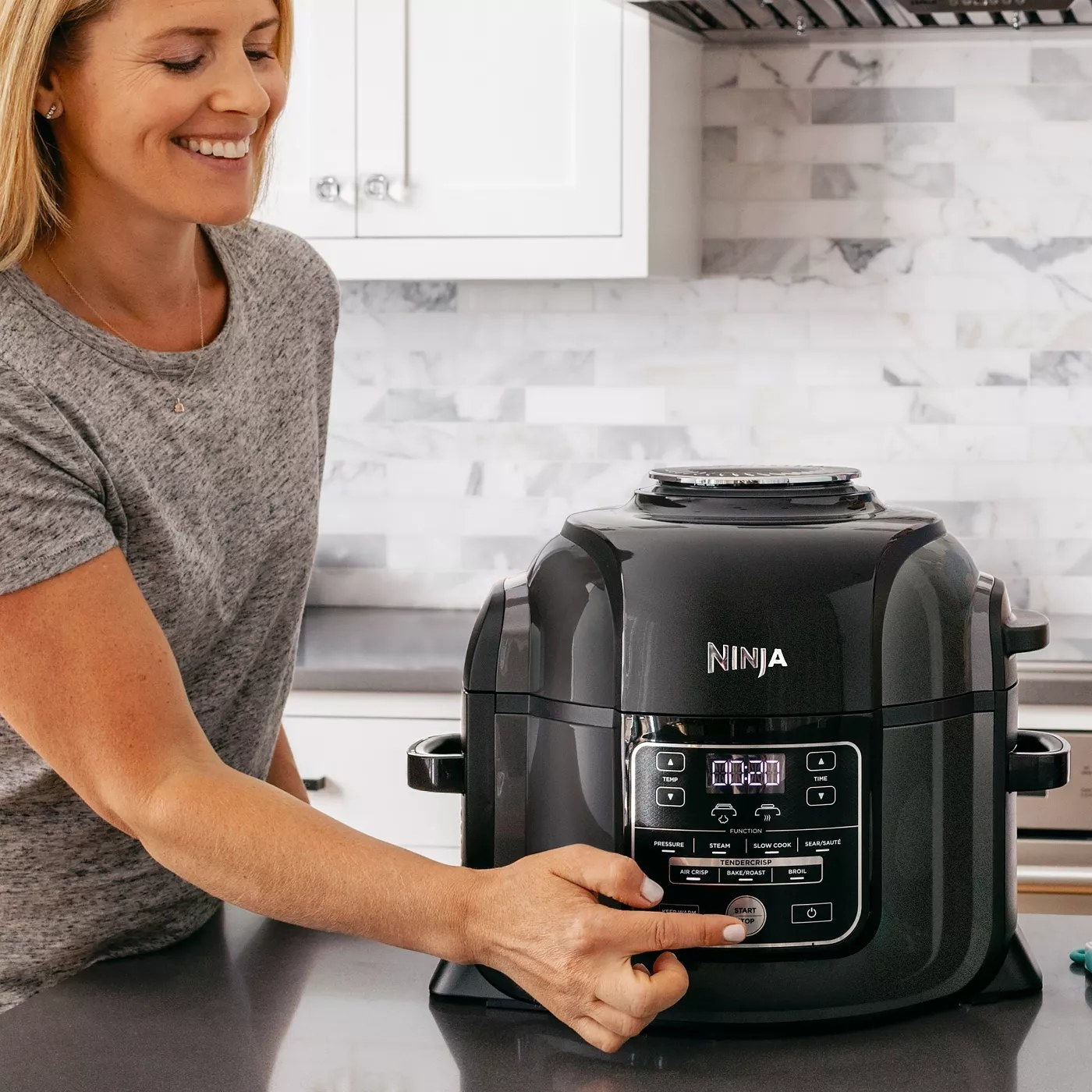 A model presses the start button on the Ninja pressure cooker and air fryer control panel