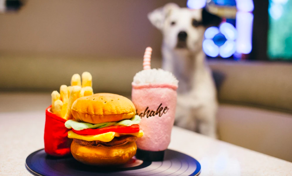 Dog standing beside a plate of plush fries, a milkshake, and burger. All pieces are removable.