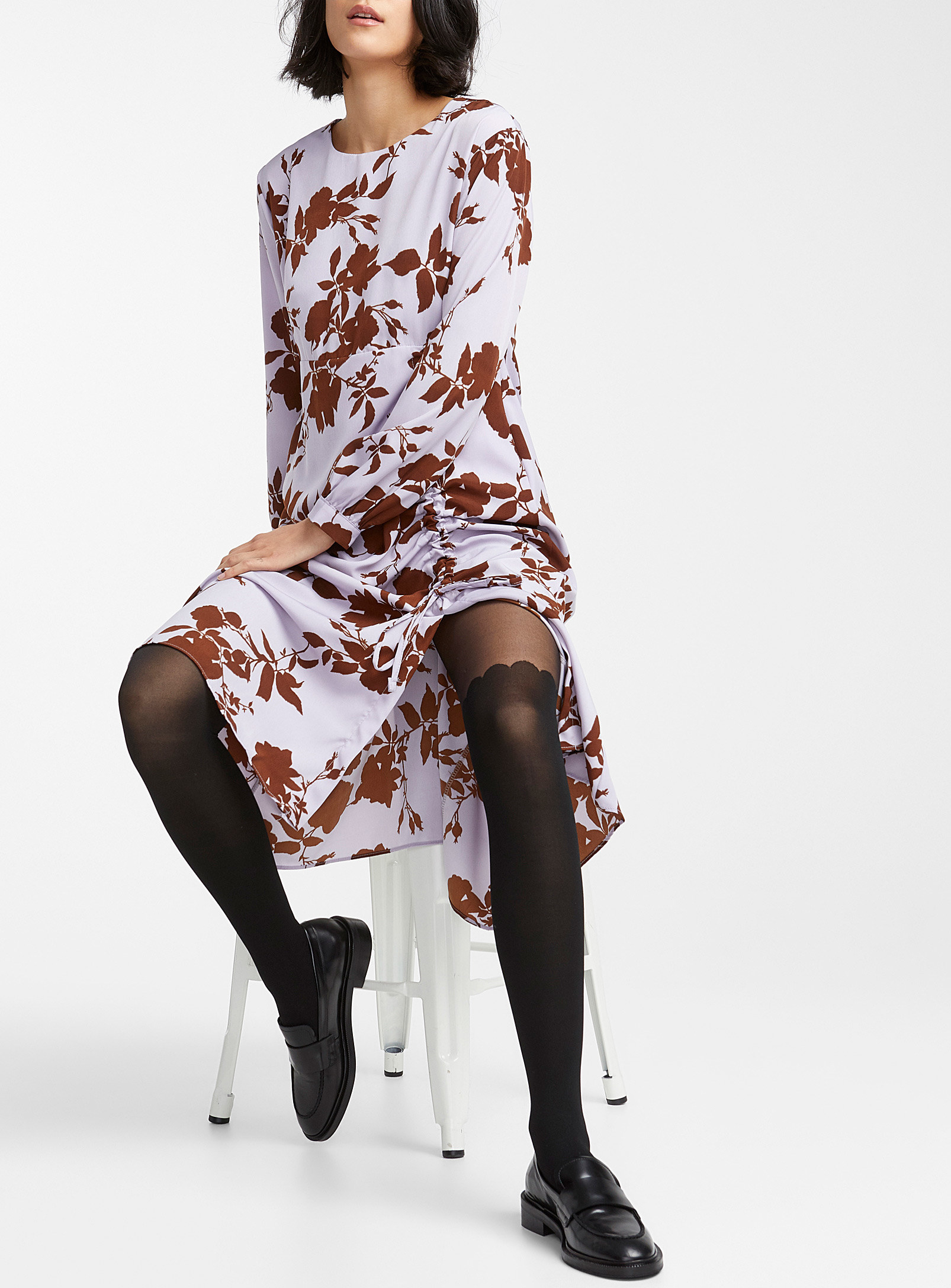 A person sitting on a stool wearing a dress and nylons with an opaque pattern that ends just over the knee