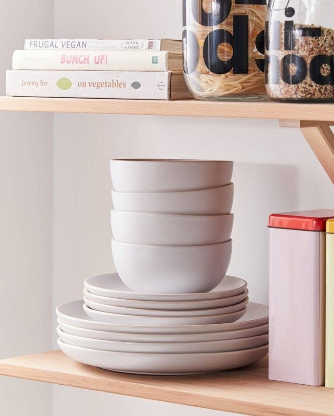 Gray stoneware plates and bowls stacked in a single pile on a wooden shelf