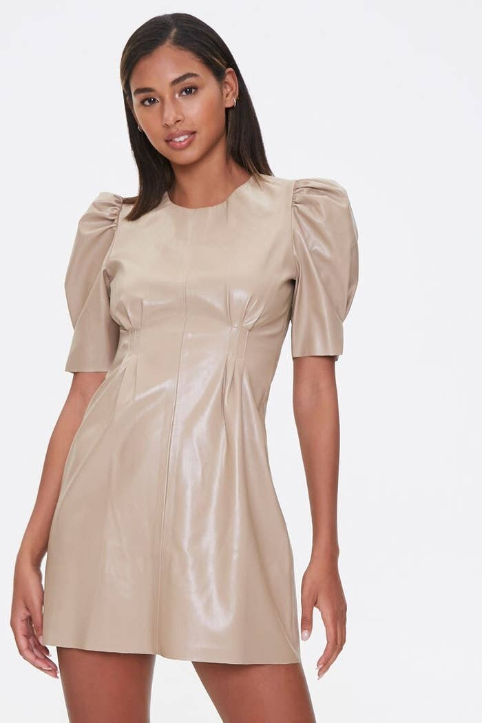 A model wearing the short-sleeve dress with dart details on the bodice in tan