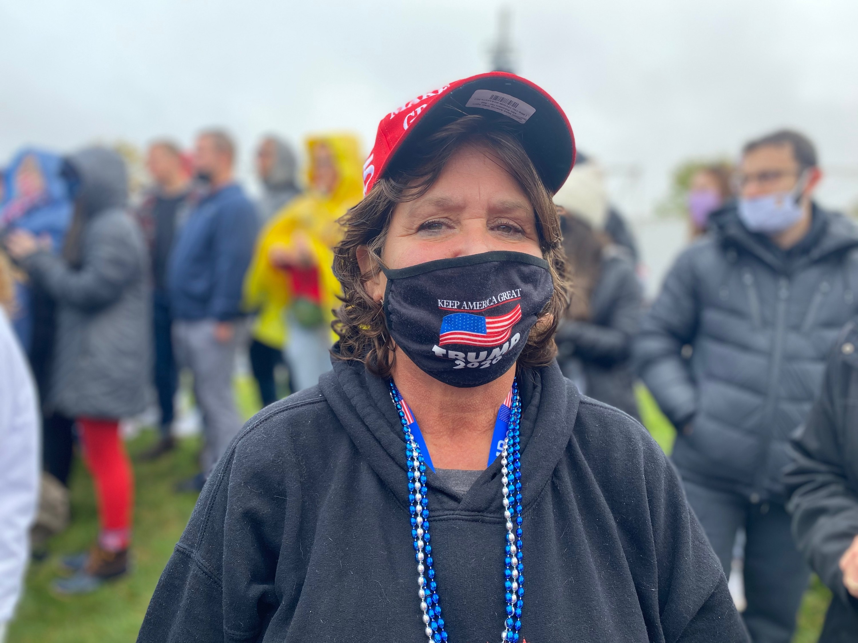 "A Trump supporter wears a ""Keep America Great, Trump 2020"" mask"