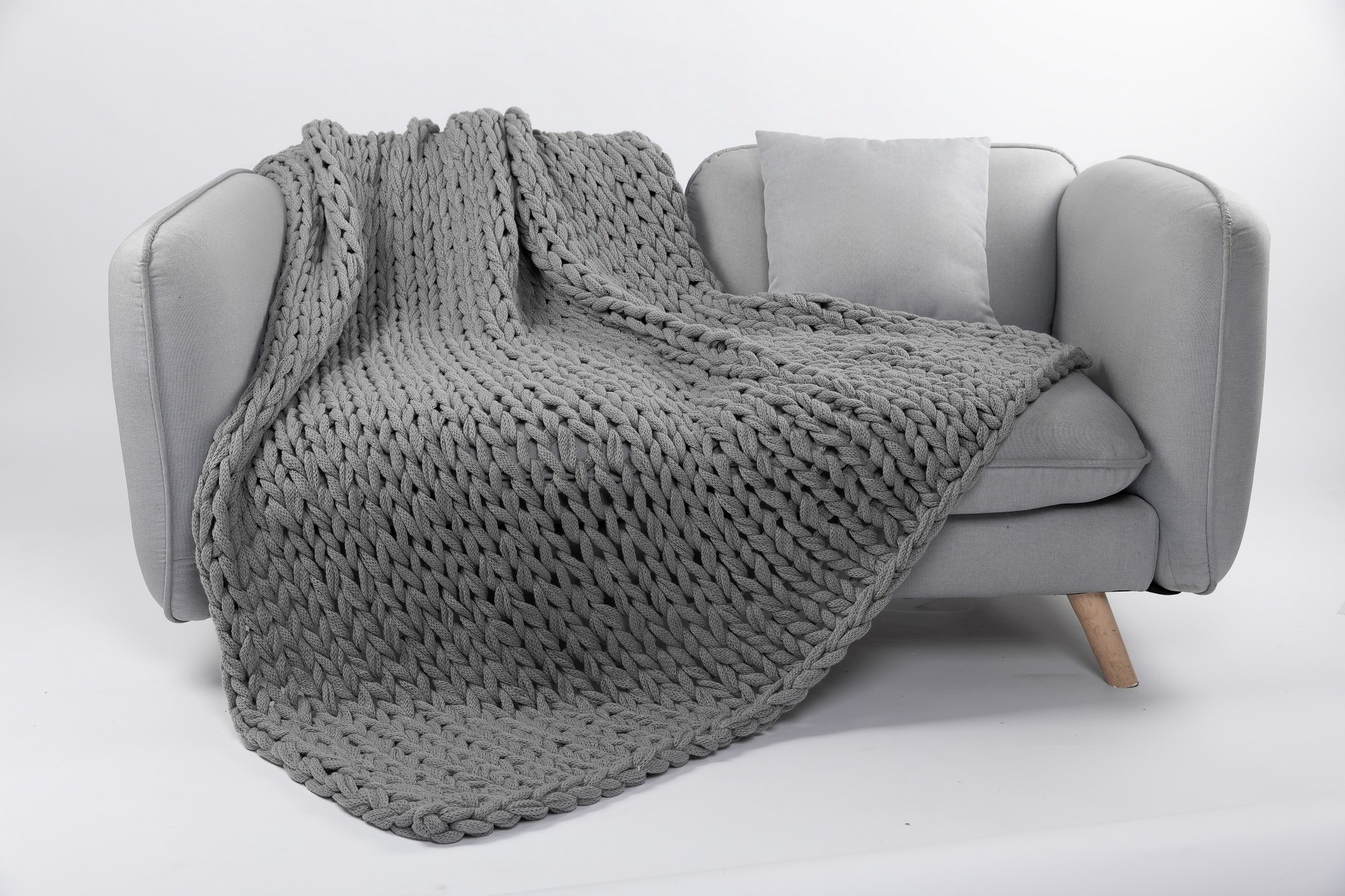 The grey blanket on a grey couch