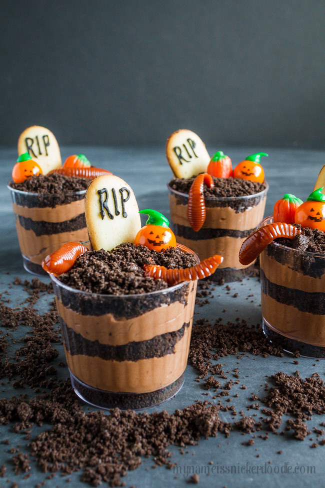 A handful of pudding and Oreo crumble graveyard cups with gummy worms and cookies on top.