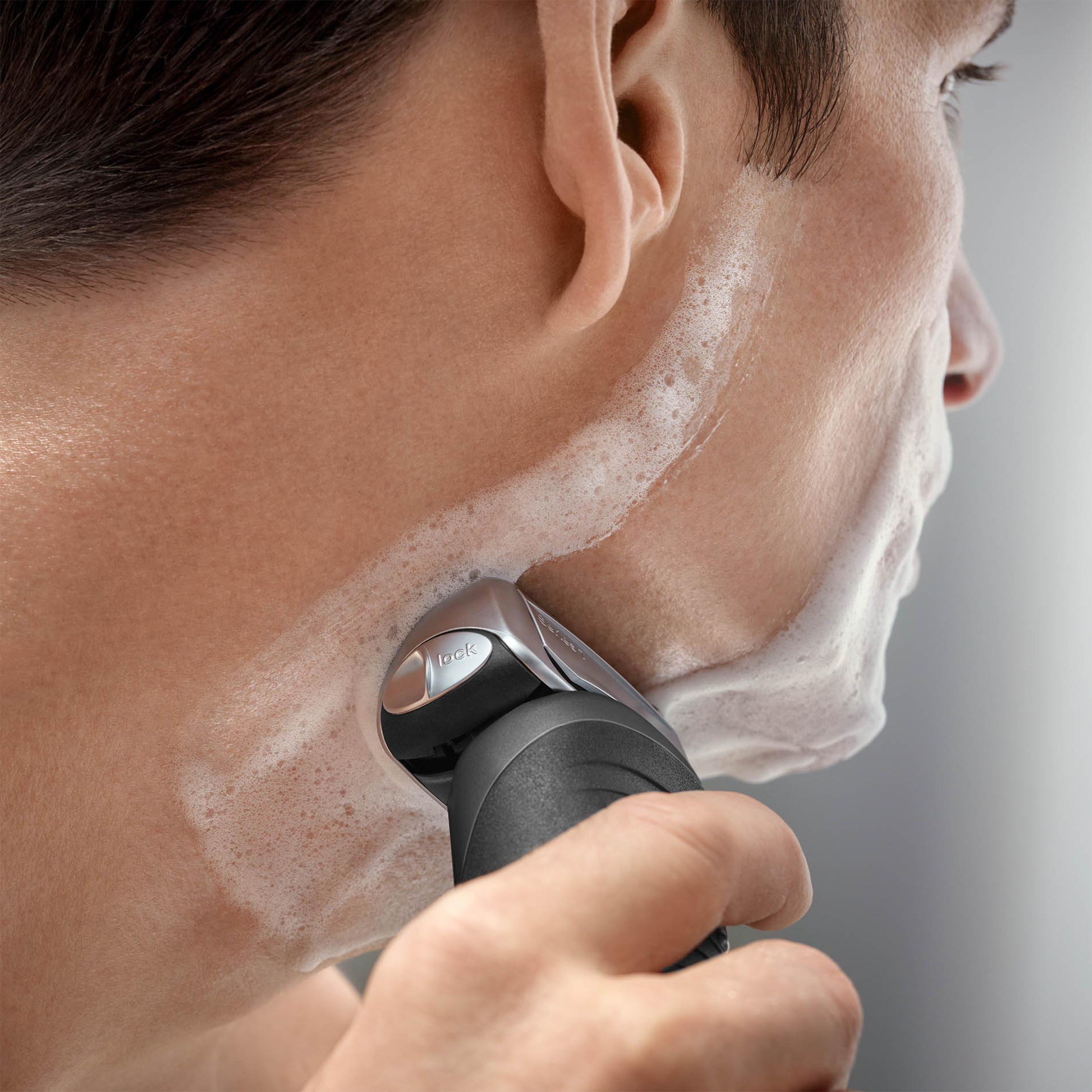 A model using the shaver on their beard