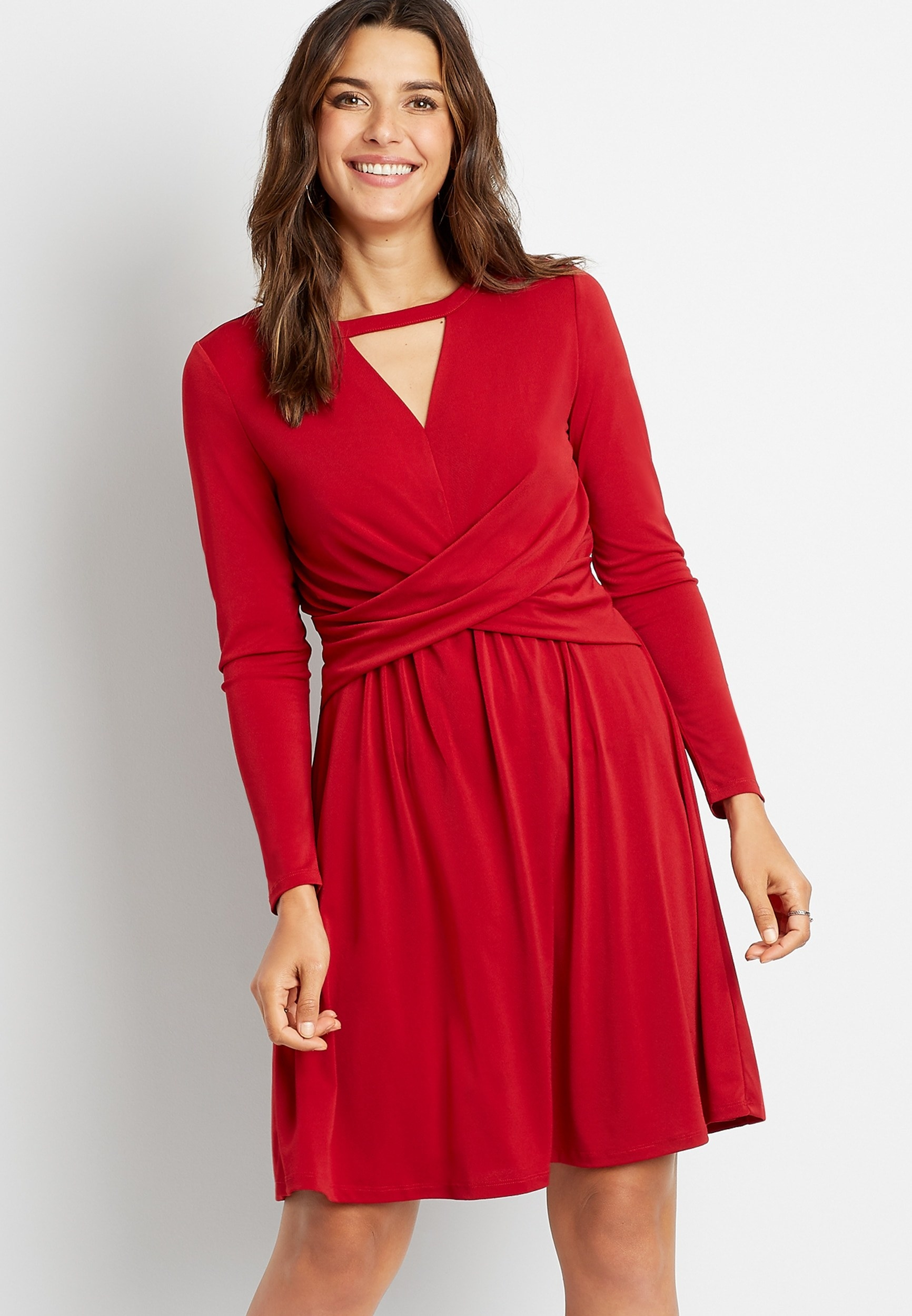 A model wearing the long-sleeve red dress with a triangular cutout at the neck and twist detail at the waist