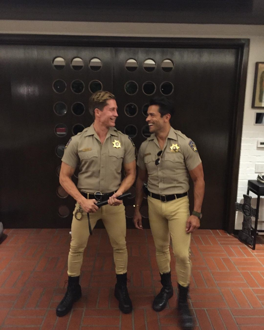 Mark Consuelos posing in an law enforcement costume next to a man wearing a similar outfit