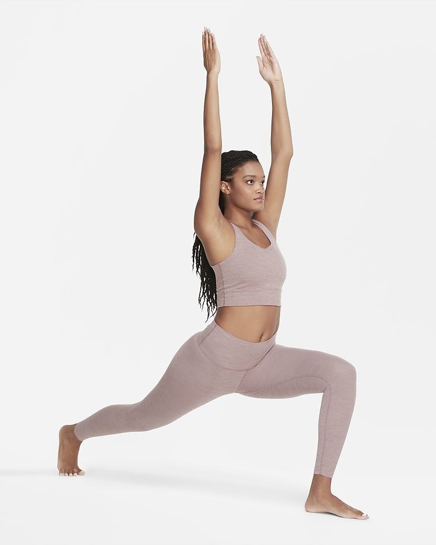 A model does a yoga pose in the smoky mauve yoga luxe leggings