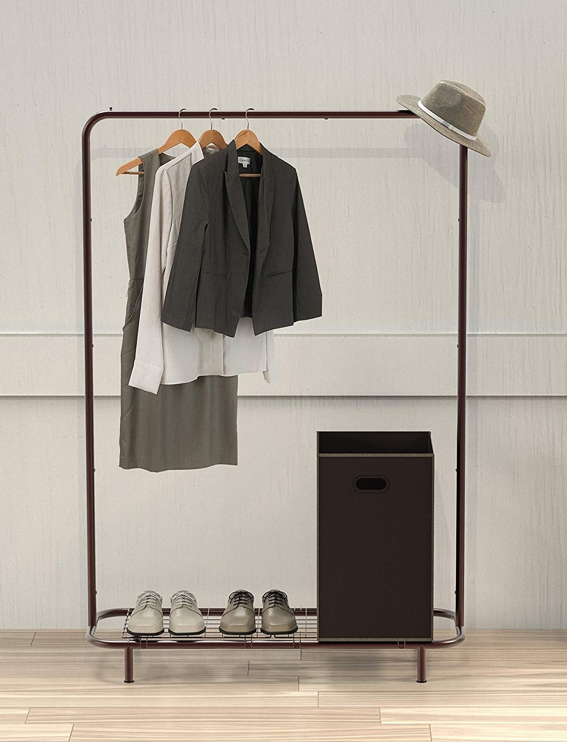Several articles of clothing hanging on a garment rack with shoes and a bin resting on the attached bottom wire shelf