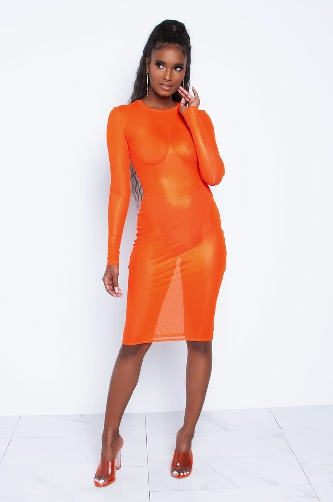 A model wearing the sheer orange long-sleeve dress, which hits at the knee