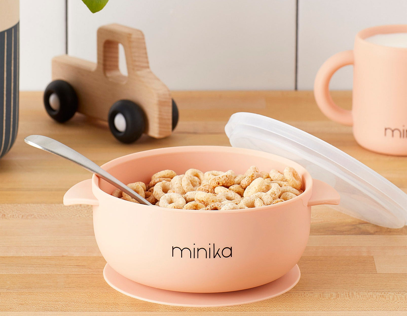 A small silicone bowl stuck to a wooden table and filled with Cheerios