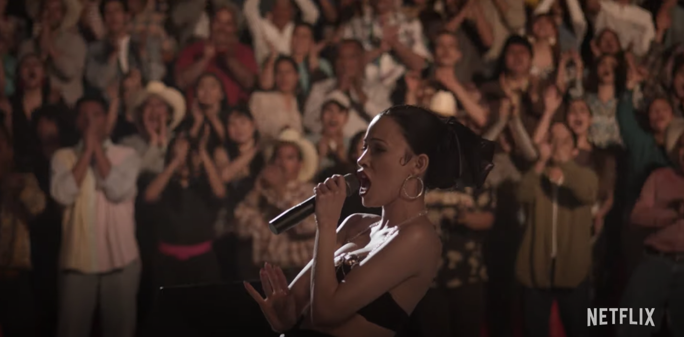 Christian Serratos as Selena performing in front of a large crowd