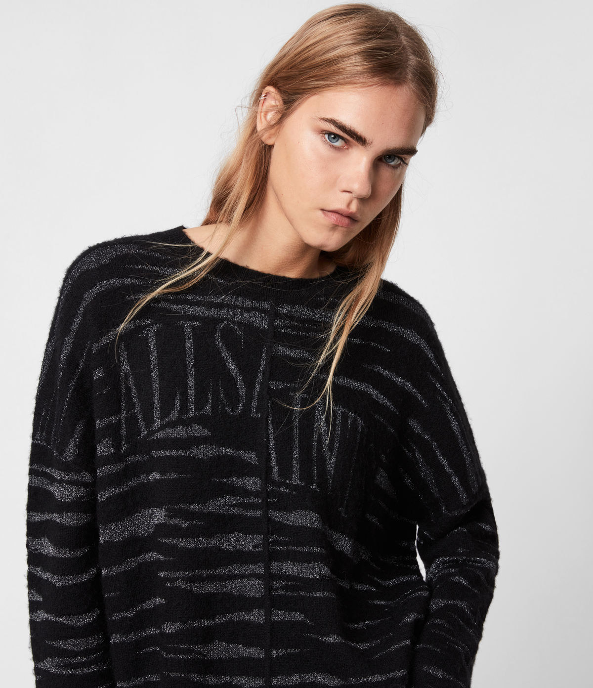 a model in a black and grey tiger print sweater with all saints written on the front