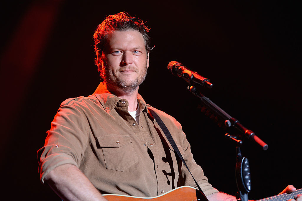 Blake Shelton performing onstage and playing the guitar