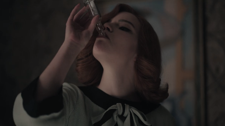 Anya Taylor-Joy as Beth Harmon takes a sip of alcohol