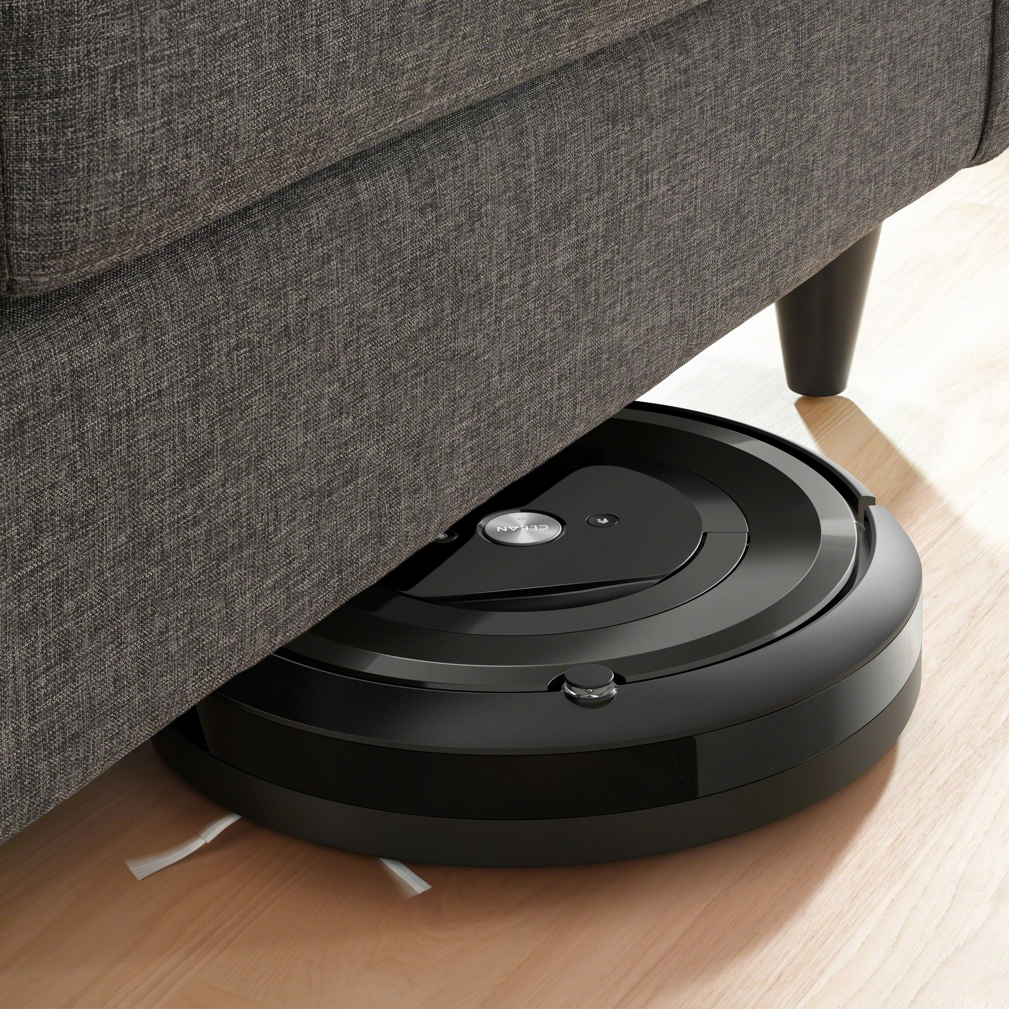 The round black vacuum, half underneath a couch
