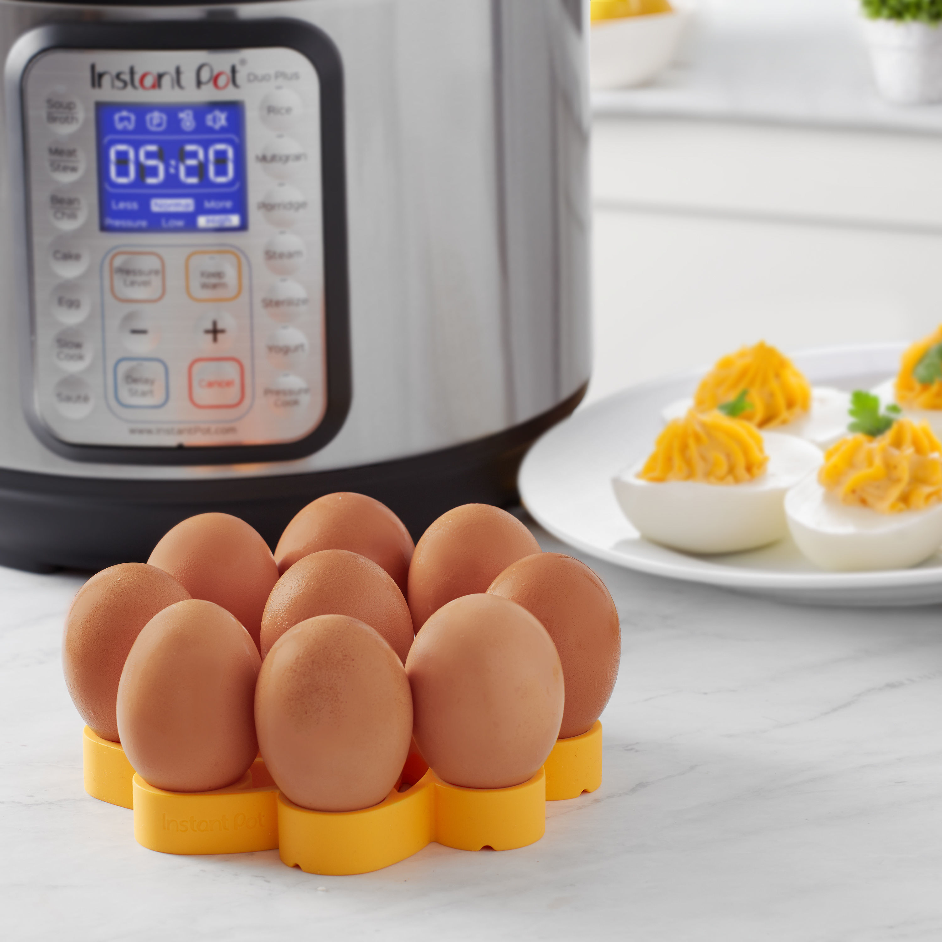 The rack, full of eggs in front of an Instant Pot and a plate of deviled eggs