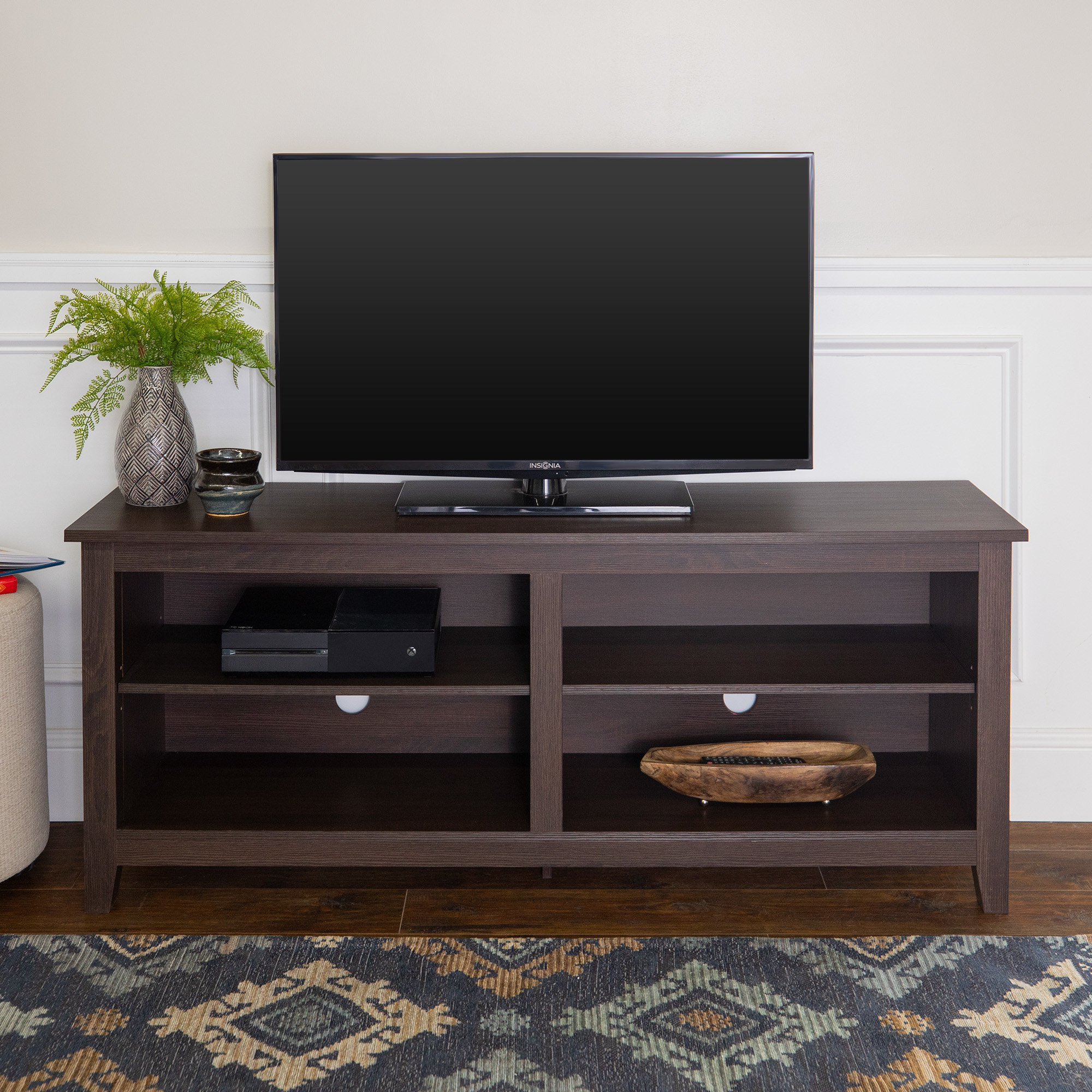The dark brown stand with a TV and knickknacks