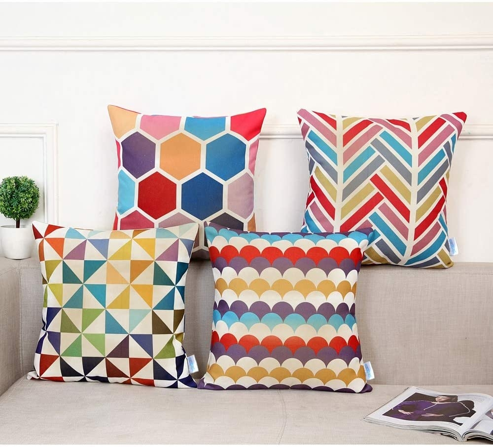 A grey couch with four colorful, pattern-covered pillows on it: one has a honeycomb pattern, one a chevron, one a pinwheel and one a fishscale.