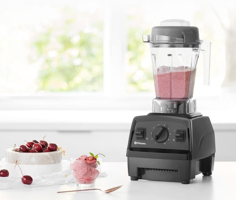 The blender on a counter next to some cherries