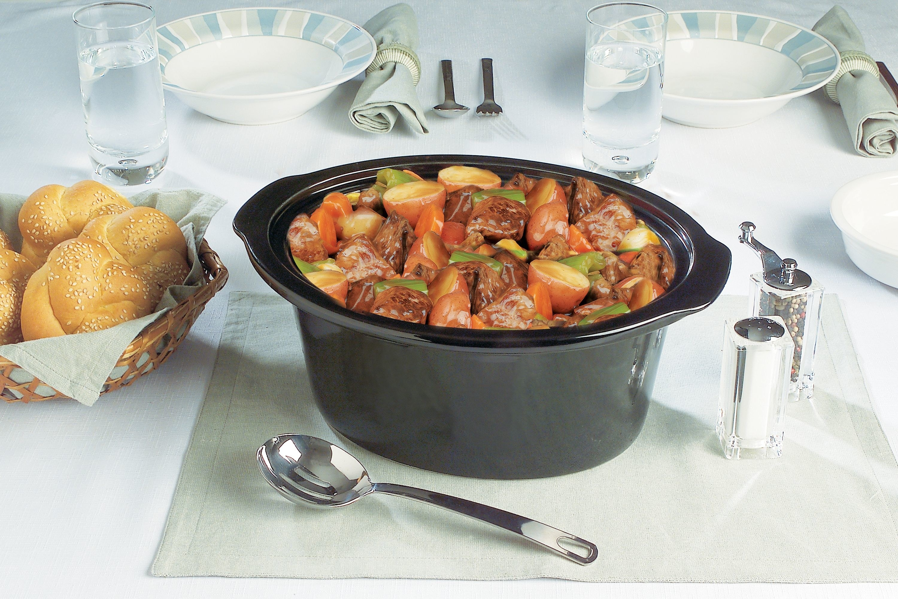 The slow cooker filled with stew on a dinner table