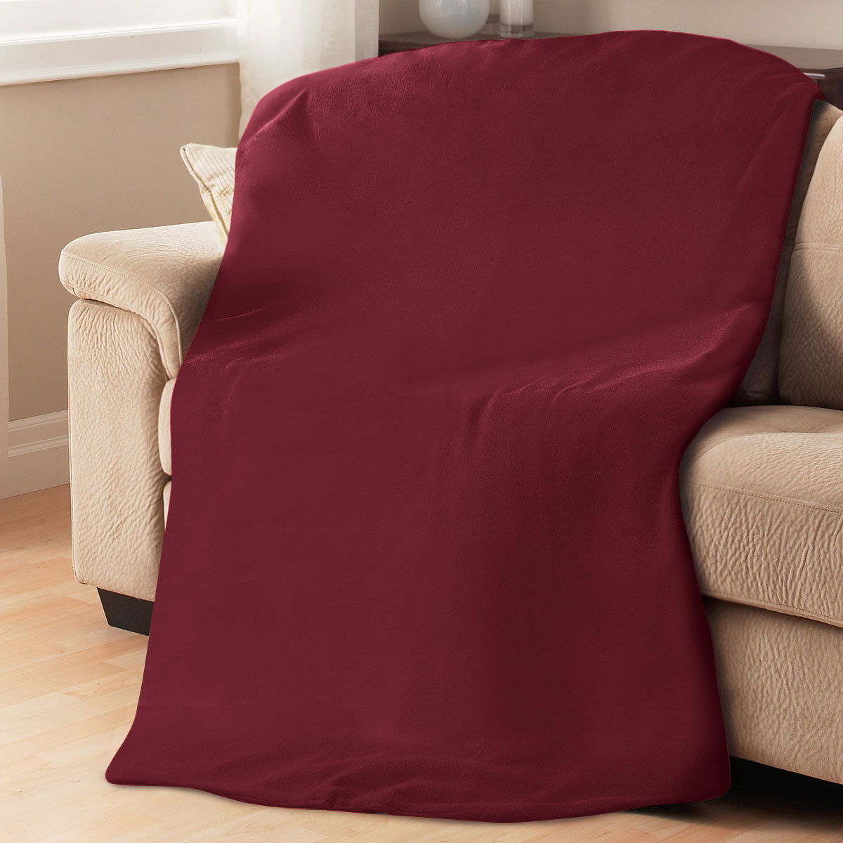 The red blanket on a tan couch