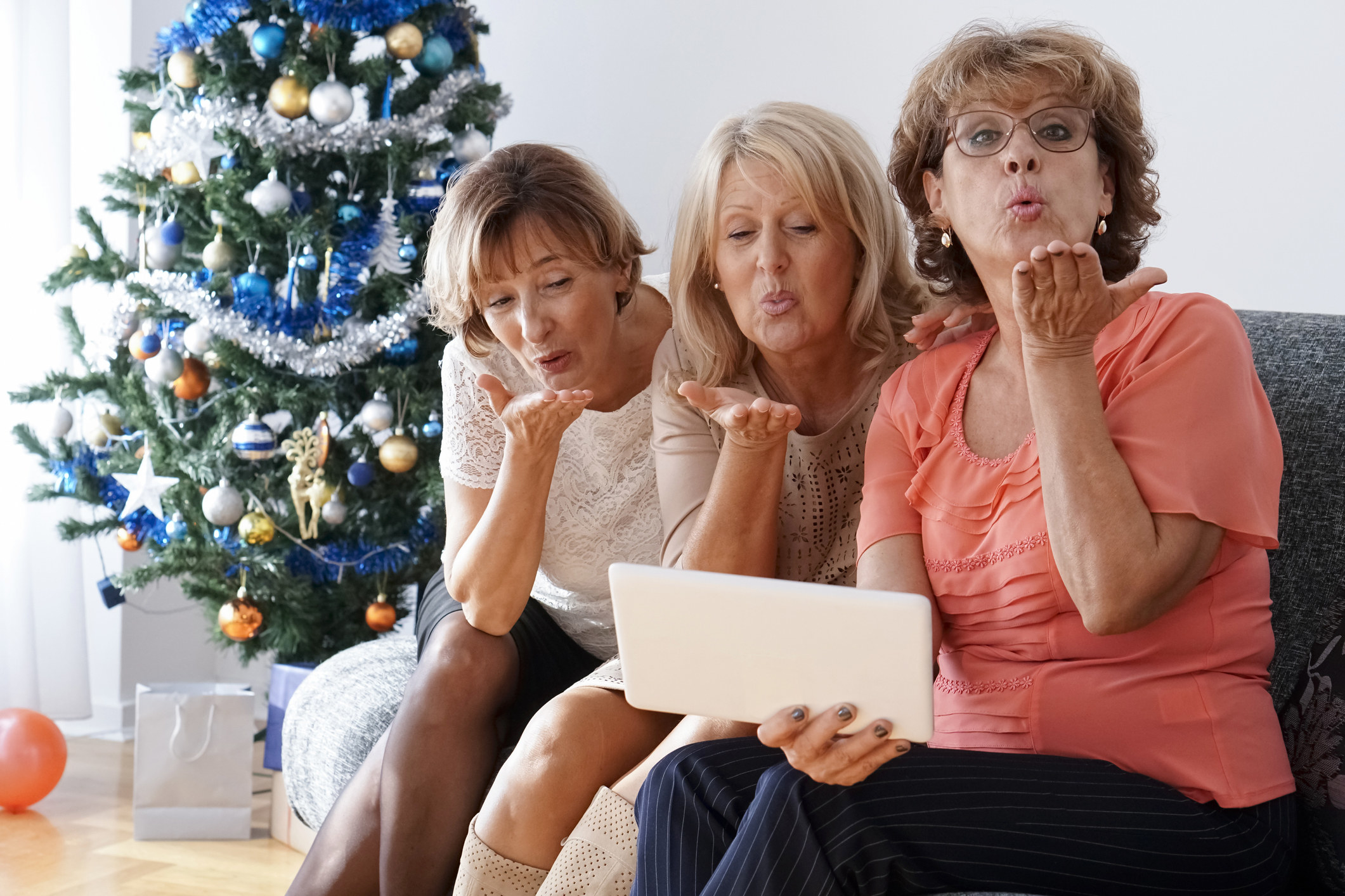 Three women sitting on a couch, with a Christmas tree in the background, blowing kisses