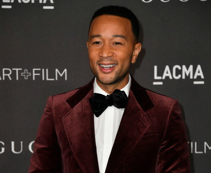 John Legend smiles while posing on the red carpet