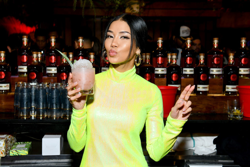 Jhené Aiko holding a cocktail while standing in front of several bottles of alcohol