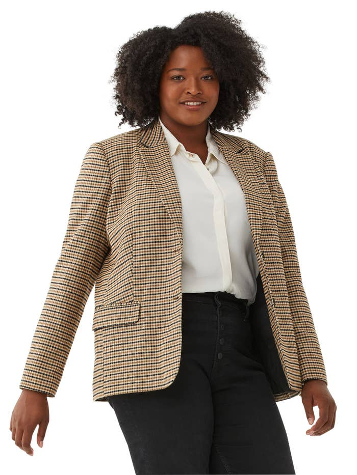 Model wearing plaid blazer with white shirt and black pants