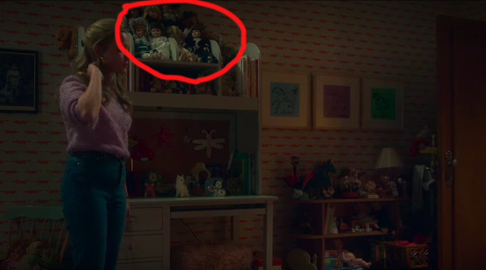 Amelia Bea Smith as Flora standing in a room next to bureau that has a large collection of dolls