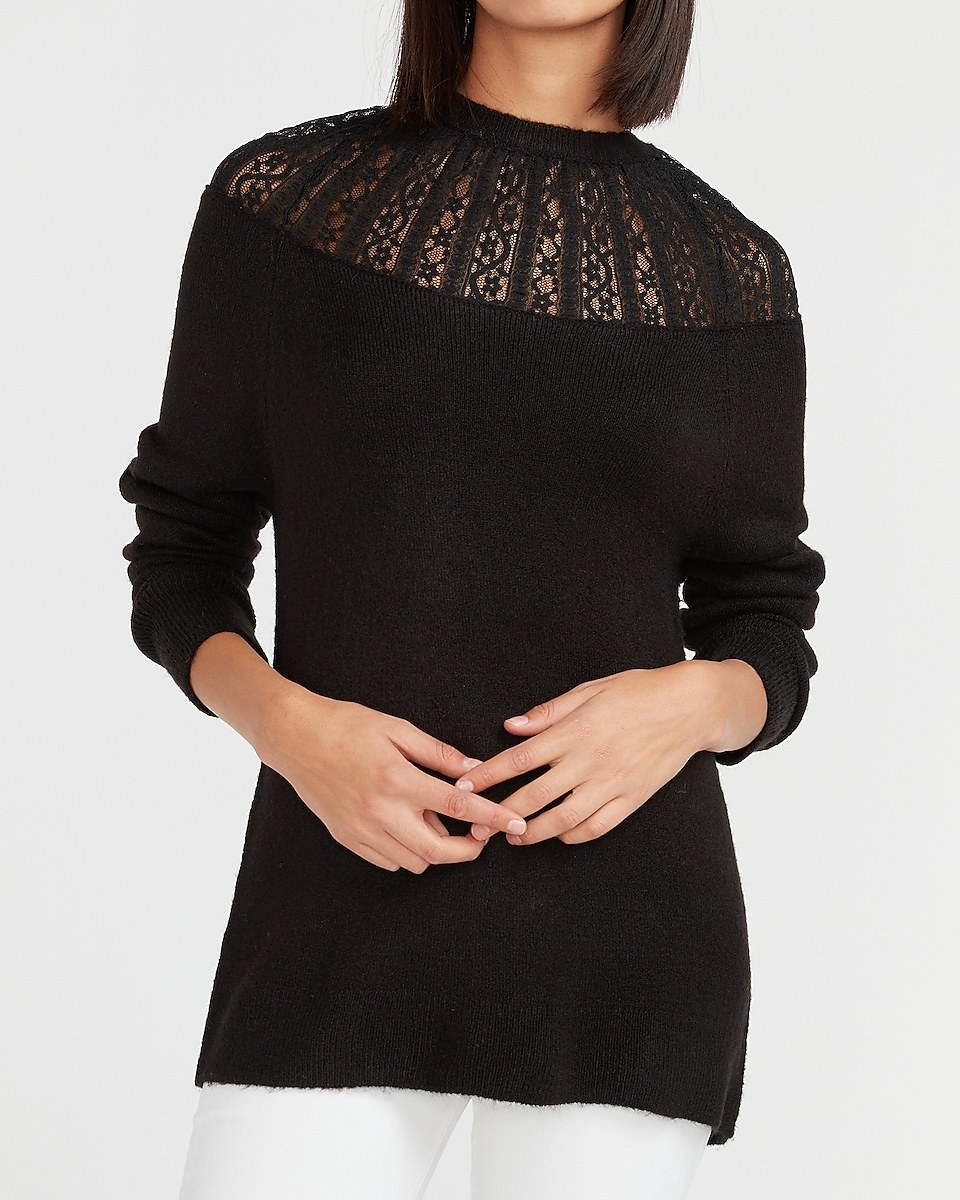 a model in a black sweater with a lace accent on top